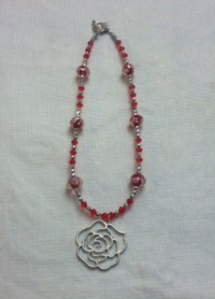 Rose pendant with ruby-colored crystals and silver accents