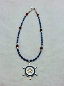 Nautical pendant with accents of silver, dark red, and blue pearl beads.